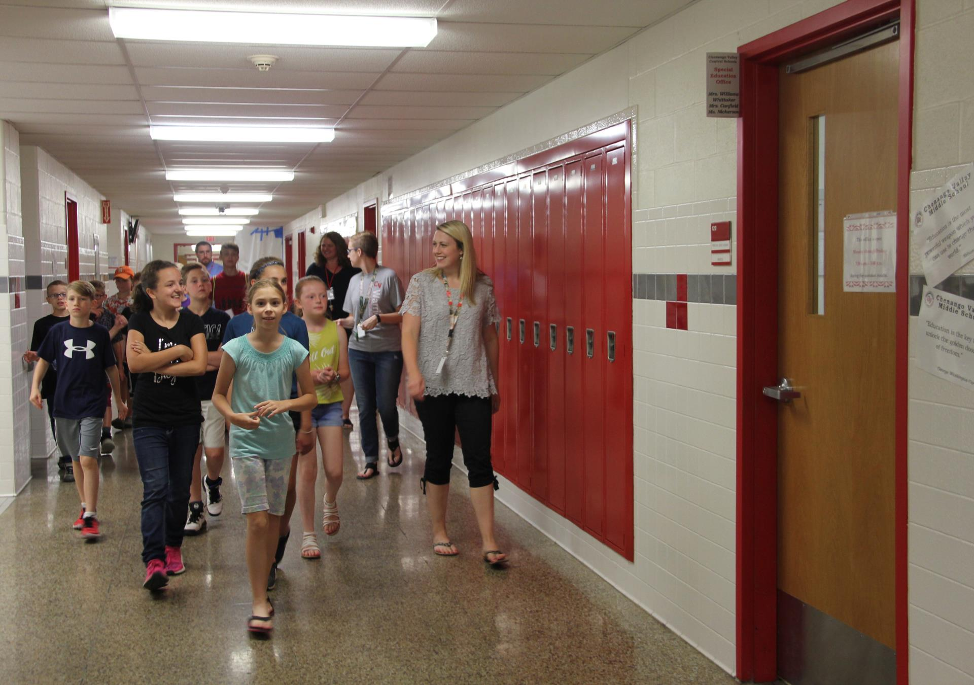 students and teachers touring hallway