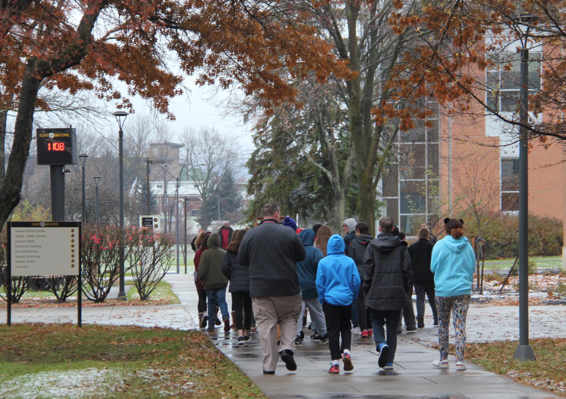 students and teacher walking on campus