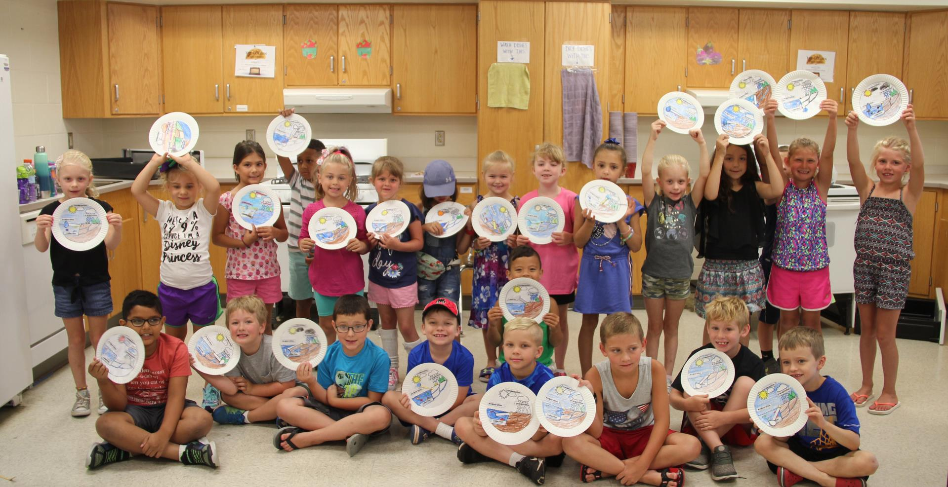 students holding water cycle diagrams