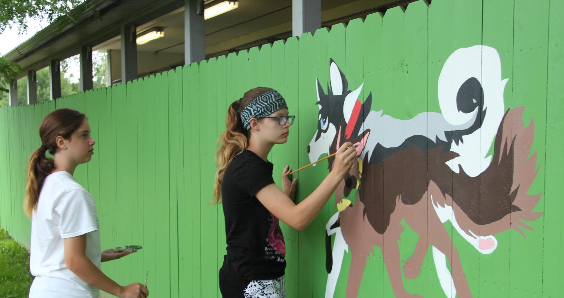 students painting dogs on mural