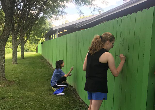students painting on green fence