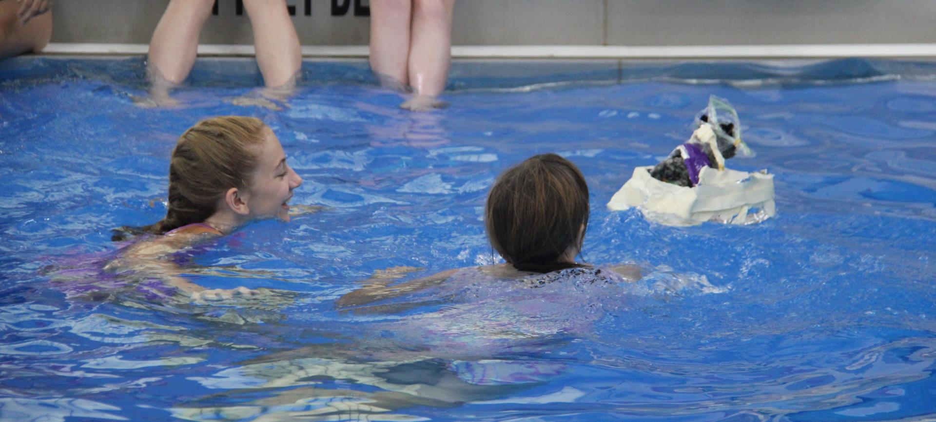 students using raft to get stuffed animal across pool