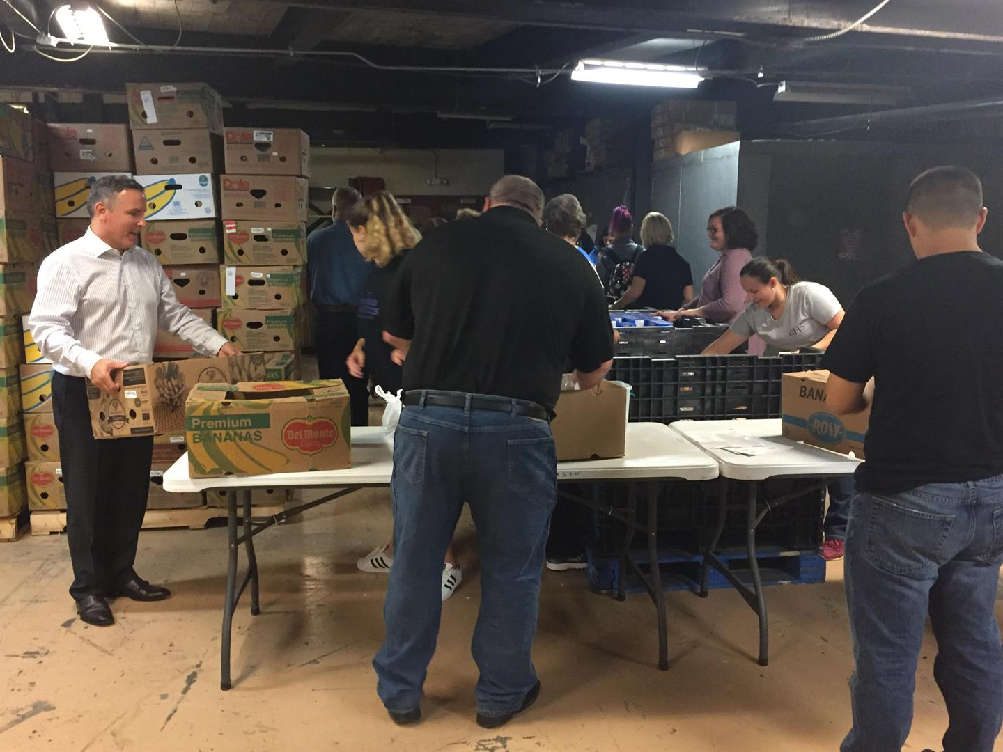 superintendent david gill helps to load boxes for food bank back pack program