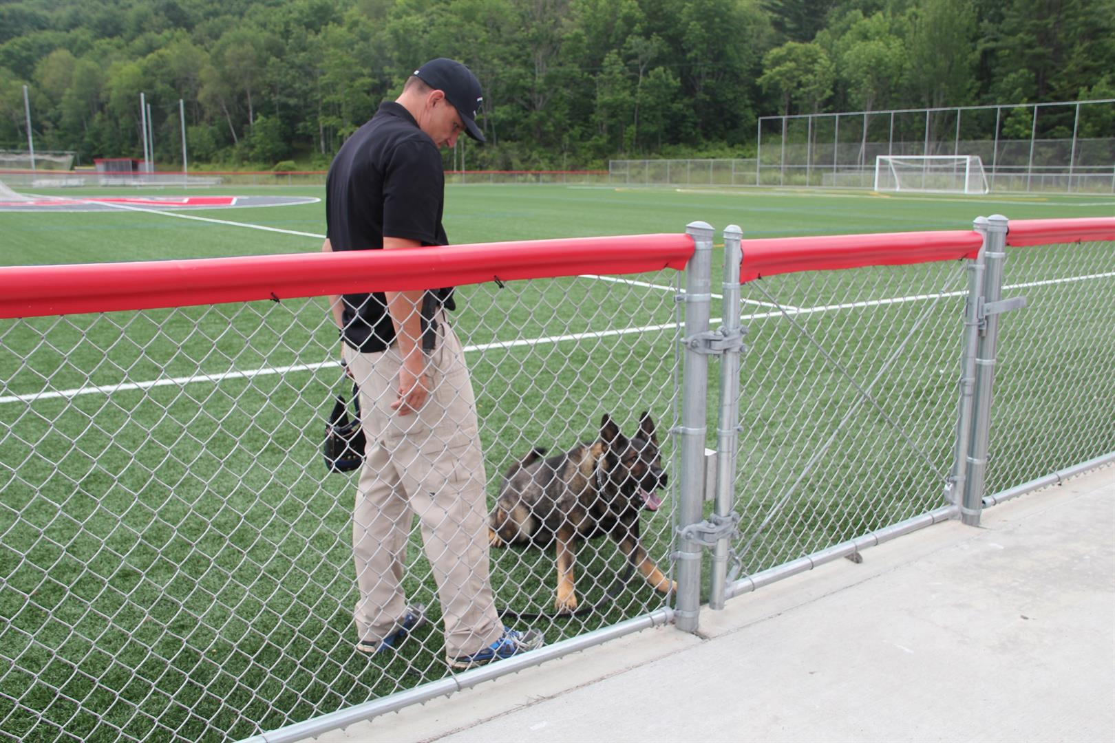 trainer and allen the k 9 police dog behind fence