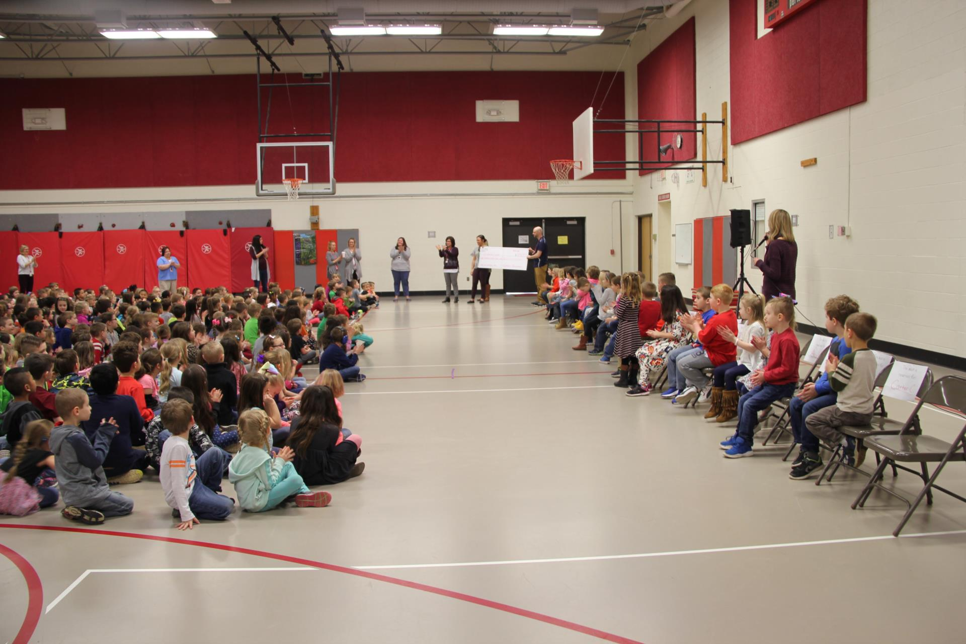 wide shot of port dickinson elementary presenting check to warrior fund
