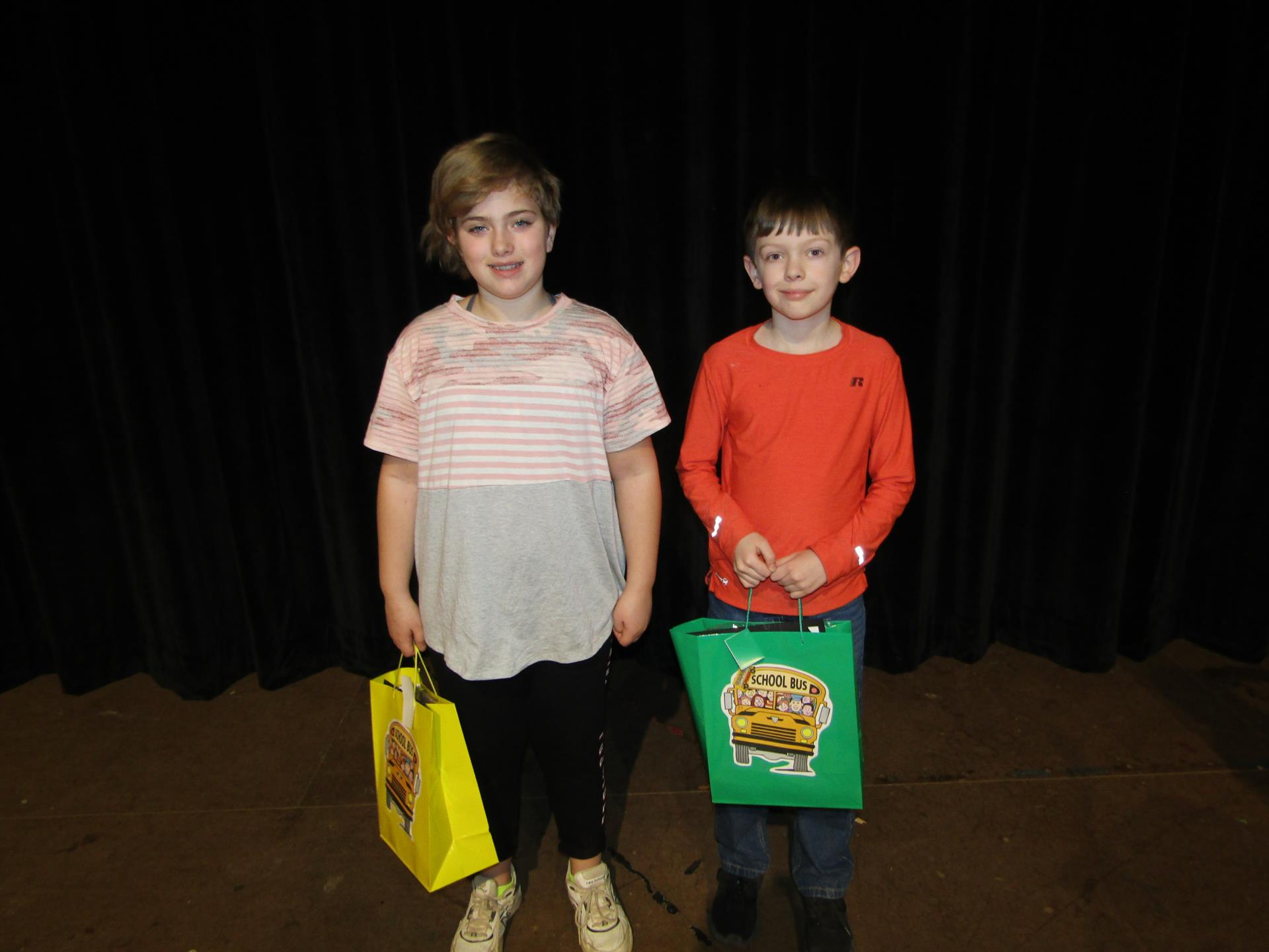 2 students holding bags for bus riders of the month