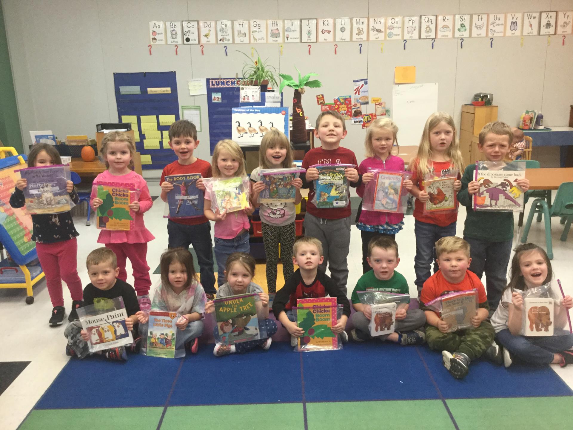 A pre-kindergarten class holds books