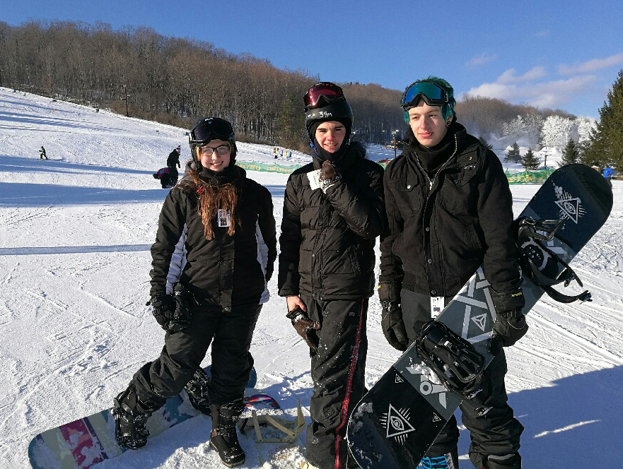 Three students pose on the slopes