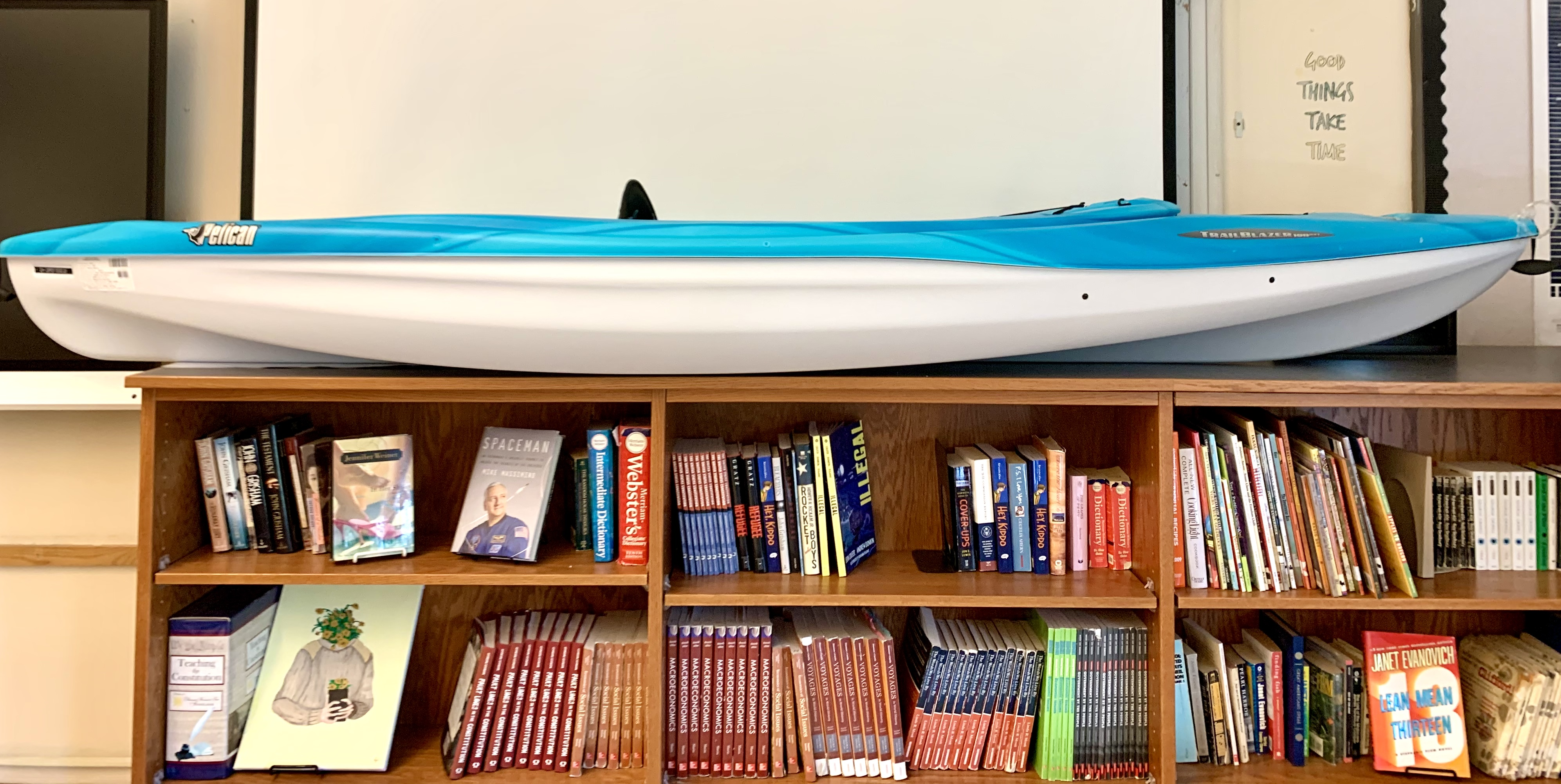 white and blue kayak rests on top of a bookshelf in a high school classroom