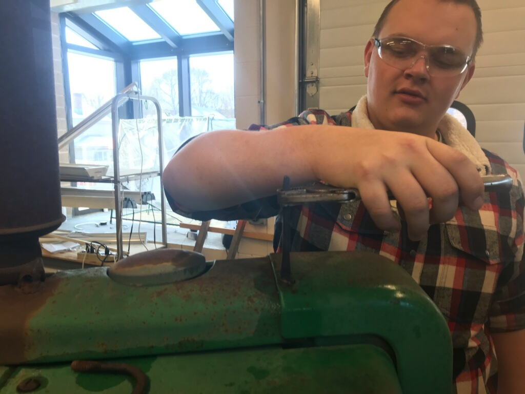 young man  with safety glasses holds wrench over green tractor