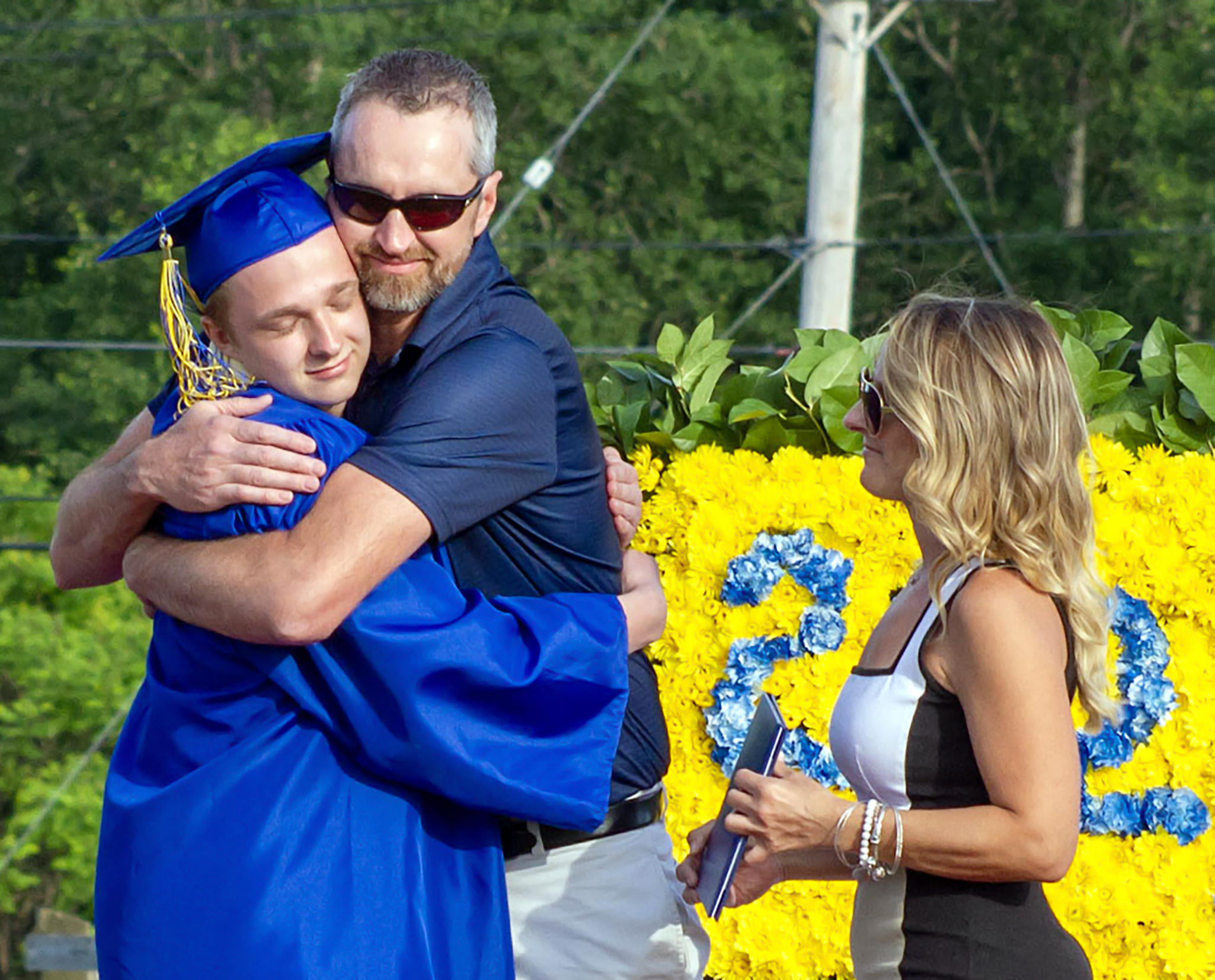 Graduate hugging father with mother on stage (6/2021)